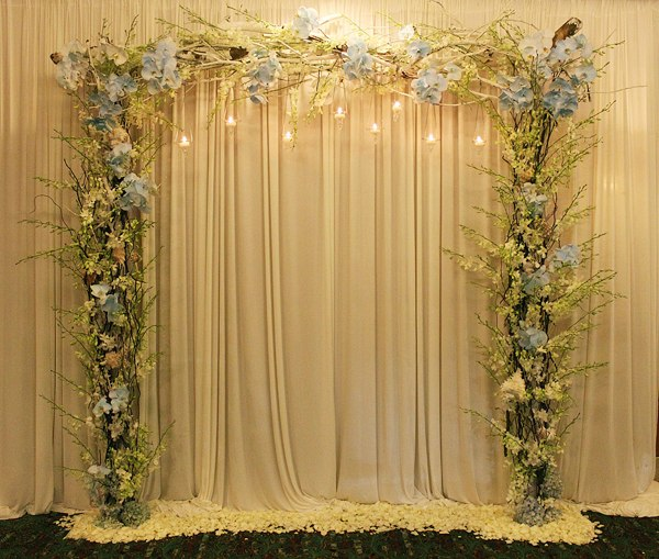 Bước vào sảnh đón khách, mọi người sẽ nhìn thấy chiếc cổng hoa với sắc xanh nhạt như màu sắc của bầu trời. Đây là nơi ghi lại những khoảng khắc đáng nhớ của khách mời và cô dâu chú rể.
