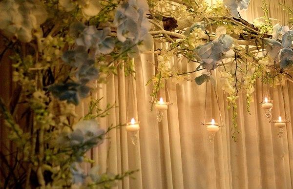 Những bông hoa lan được chuyên gia về hoa cưới nhuộm màu tinh tế, khéo léo. Đi kèm với hoa còn có những chiếc cốc nến treo làm tăng thêm vẻ đẹp lung linh.
