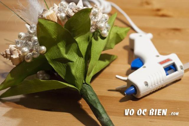 xếp lá hoa che lại phần đuôi của bó hoa sao cho lá xòe đều về cac hướng