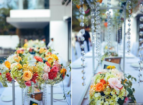 Làm đẹp cho giàn hoa là những dải pha lê lấp lánh, rủ mềm mại. Thiết kế hoa dạng treo, độ cao vừa phải và được tính toán tỉ mỉ để không chắn tầm nhìn của khách mời.