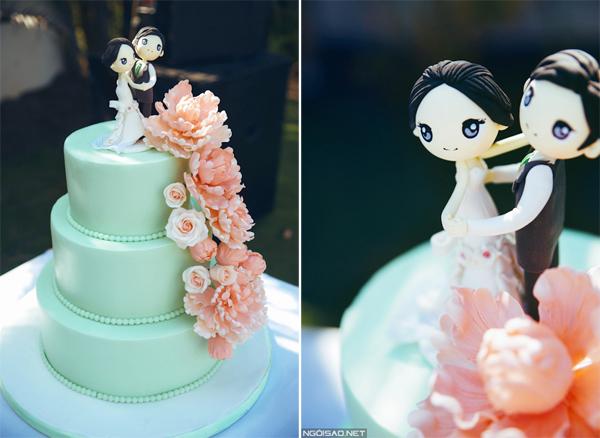 Bánh cưới mang sắc xanh nhẹ nhàng, tô điểm bởi hoa gam màu hồng đào, ton sur ton cùng hoa trang trí trên bàn tiệc. Cake topper hình cô dâu chú rể lãng mạn là điểm nhấn cho bánh cưới.