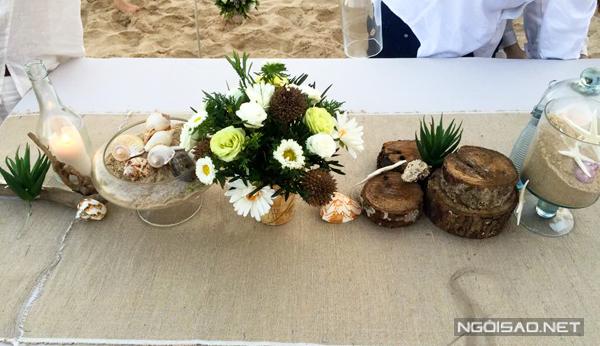 Màu sắc ấm áp của gỗ, màu của ốc biển kết hợp cùng cát, cây cỏ và nến làm đám cưới thêm lung linh.