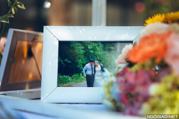 Những bức ảnh cưới của cô dâu chú rể được đặt xen kẽ cùng hoa trên bàn tiệc.